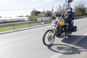 "Antalya, Turkey - November 23, 2014: Happy bikers does the typical greeting riding Harley Davidson at motorcycle rally ""Alanya Tour"" by Antalya Chapter. Photo was taken at Antalya-Alanya Road in the Antalya in the Turkey. This guy Harley Owners Group Antalya Chapter member"
